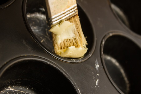 greasing: engrasar la forma de hornear muffins Foto de archivo