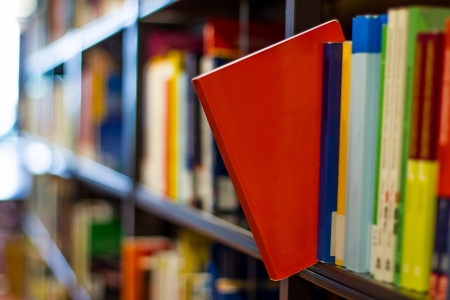 rode boek knallen uit een boekenplank