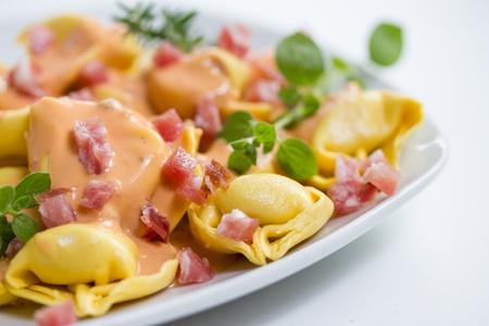 pancetta cubetti: tortellini freschi in salsa leggera con prosciutto Archivio Fotografico