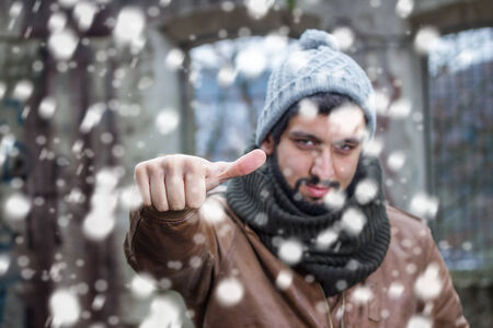 thumps up: smiling beard man making thumps up in snowfall