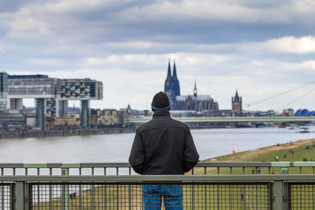 man looking at cologne rhine buildings photo