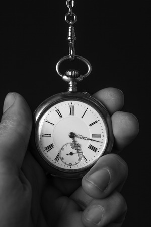 classical mechanics: old pocket watch in black and white in human hand