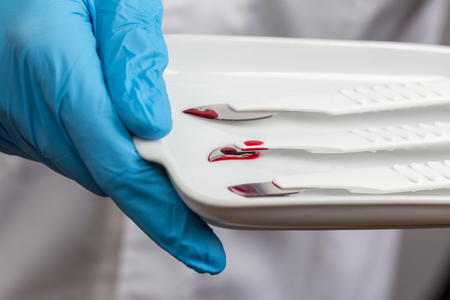 scalpels: surgeon with a sharp used scalpels in his hands Stock Photo