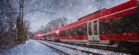 red train speeding in the snow Stock Photo