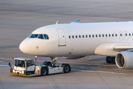passenger airplane beeing towed at an airport