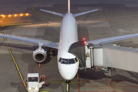 airplane at an airport gate at night Stock Photo