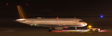an airplane beeing towed at night at an airport