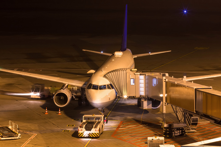 an airplane at night at an airport gate Stockfoto