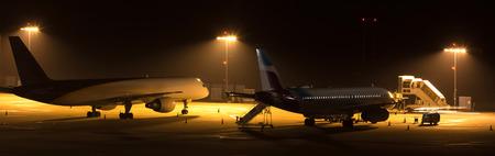 airplanes at an airport at night
