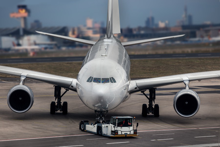 an airplane beeing towed at an airport composing Stockfoto