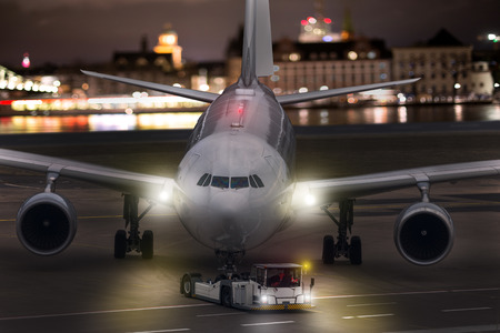 an airplane beeing towed at an airport at night composing