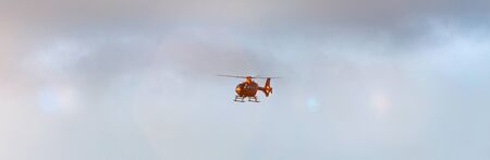 a helicopter flying in a cloudscape