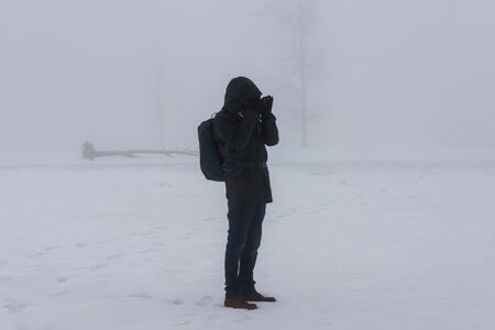 photographer in an foggy winter landscape panorama
