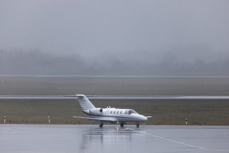 a private jet on an rainy airport