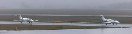 two private jets on an rainy airport panorama