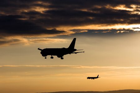 passenger airplanes landing in the evening sun