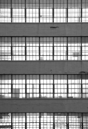 Black and white image of a stack of office windows. Light shines through silhouetting office equipment.