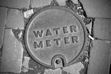 City Water Meter Lid on a cobblestone street
