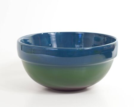 Blue, green and red painted ceramic bowl on white background.  Stock Photo