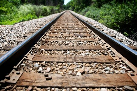 View down a long stretch of railroad tracks. Limited depth of field affects applied.