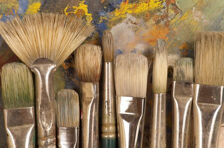 Close up of artist's brushes on an painting pallet. Imagens