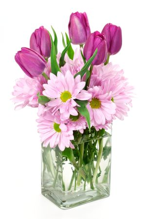 arrangment: A Spring flower arrangement of daisies and tulips in a rectangular glass vase.
