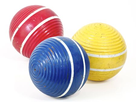 Three croquet balls, blue, red and yellow. Stock Photo