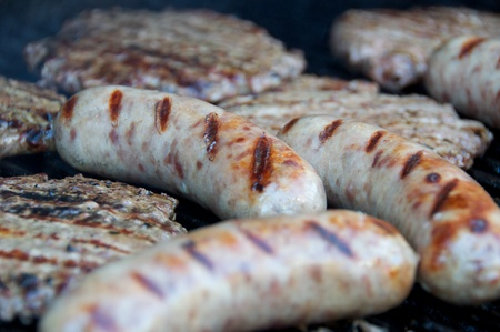 Bratwurst and hamburgers cooking on the grill. Stock Photo