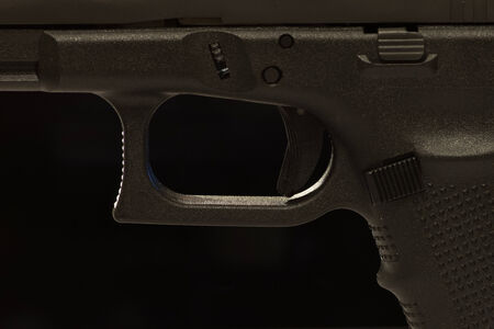 A closeup view of a semi-automatic pistol trigger. On black background.