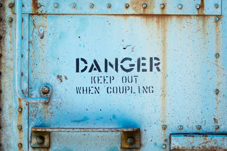 out of danger: The side of a train car with the word Danger keep out when coupling. Stock Photo