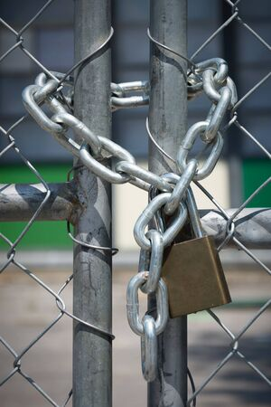 keep gate closed: A chain and pad lock secures an entry way fence. Stock Photo