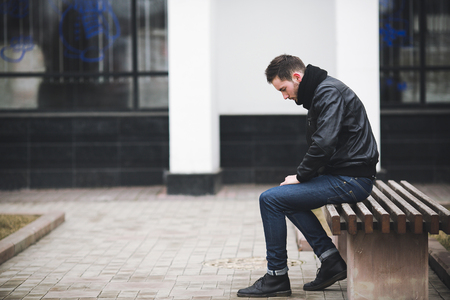 A man dressed in jeans and black jacket seats on a bench