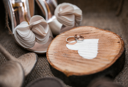 Shous and rings of bride on wooden heart photo