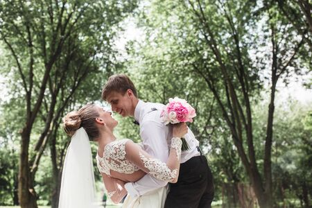 Bride and groom having fun in the woods Stock Photo