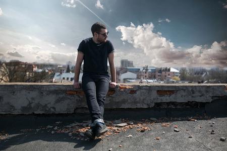 De man in de authentieke laarzen en jeans naadlijn op het dak van het gebouw in de oude stad