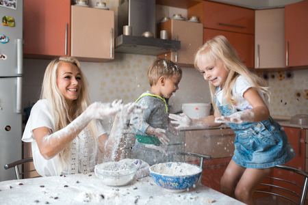mother and children playing on kitchen with flour