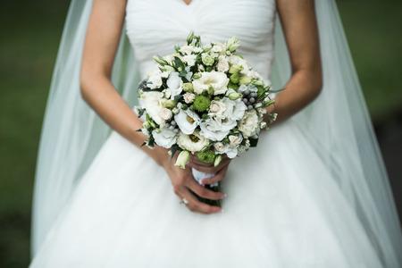 Very beautiful wedding bouquet in hands of the bride Standard-Bild