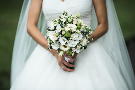 outdoor wedding: Very beautiful wedding bouquet in hands of the bride Stock Photo