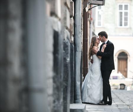 novios besandose: Encantadora pareja de boda que se besa en la ciudad