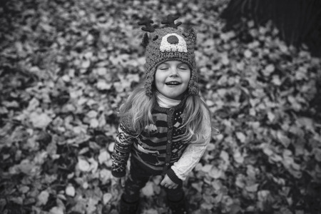 Girl laughing at the camera on a yellow leaves photo