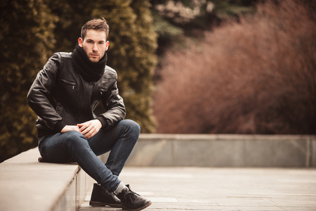 model male: A man dressed in jeans and black jacket seats on a slab