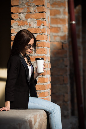 beautiful girl: Beautiful girl in glasses with coffee on the brick wall background