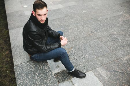 british ethnicity: A man dressed in jeans and black jacket seats on a slab
