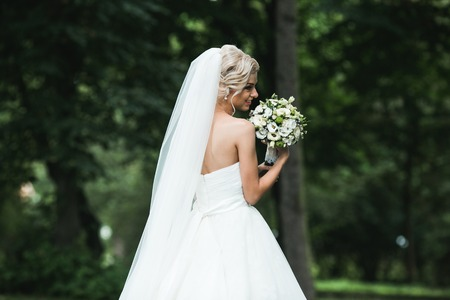 nude bride: Beautiful bride posing with bouquet in park Stock Photo