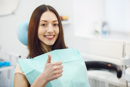 Beautiful patient sits in a chair at the dentist