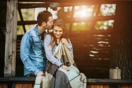 Jong paar in liefde verpakt in plaid staande Stockfoto
