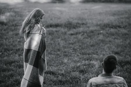 couple  amoureux: Jeune couple dans l'amour envelopp�e dans plaid debout et en regardant les uns les autres