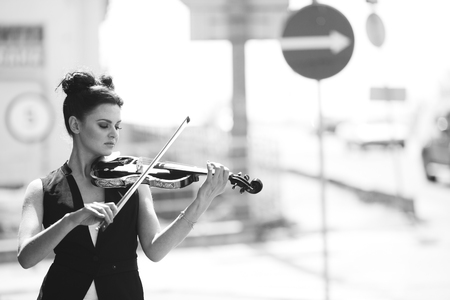 solo violinist: girl posing with violin in hand in the street Stock Photo