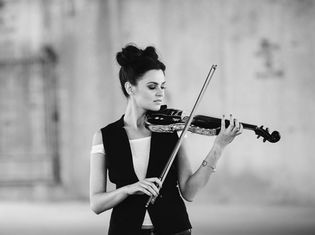 solo violinist: beautiful girl with violin posing on a parking