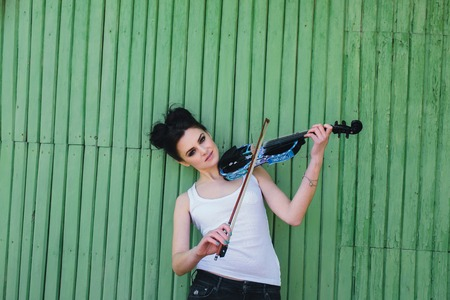 solo violinist: beautiful girl with violin posing on wall background